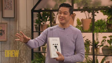 Wilson Tang holding a cookbook